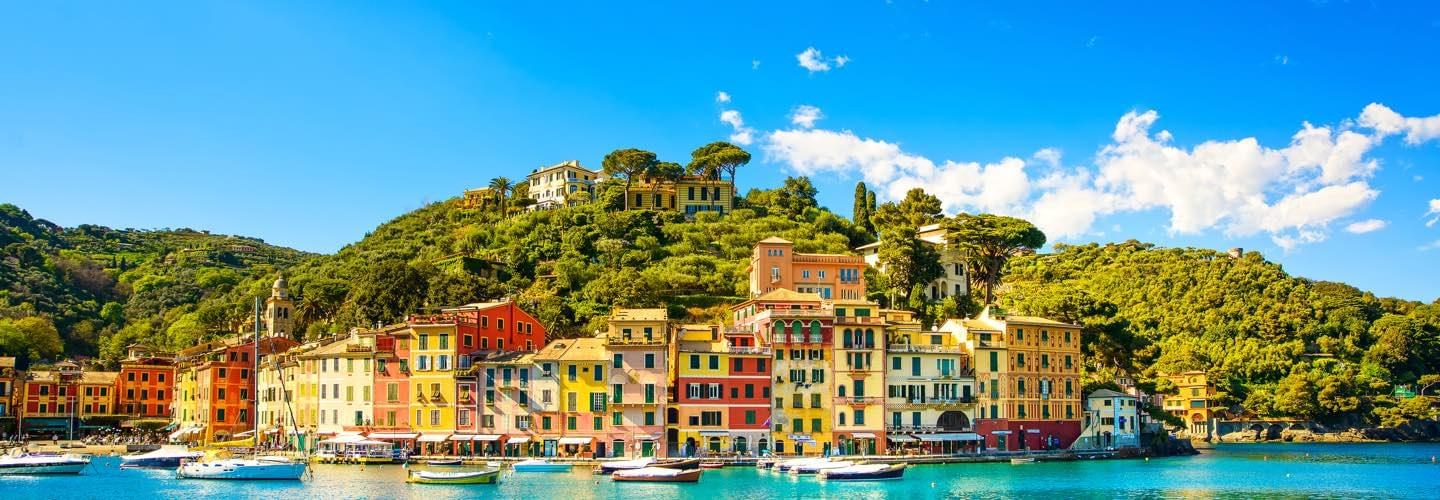 Daylight picture of Portofino in Italy with colored houses and boats with a blue cloudy sky