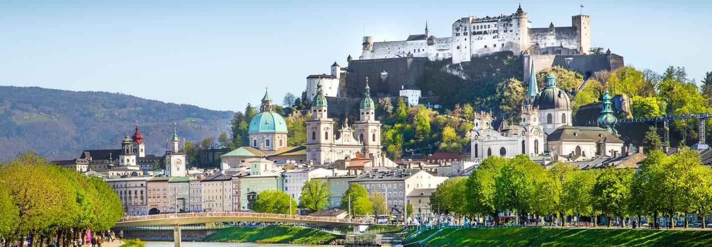 Sunny view from the Salzach river of the Hohensalzburg Castle and the Salzburg cathedral in summer