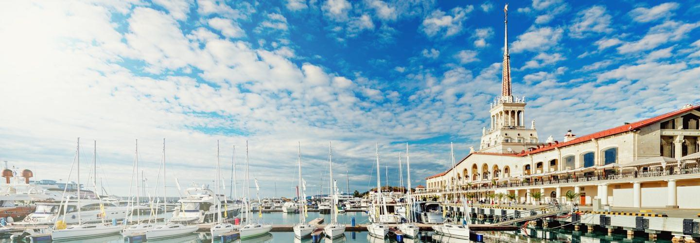 Sochi Sea Port with boats and cloudy blue sky and the Sochi Grand Marina Burevestnik Group