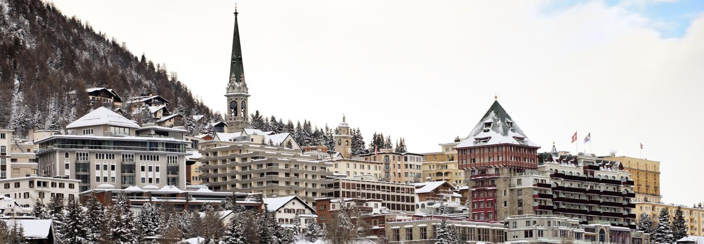Skyline of St Moritz in Switzerland with several houses and clock house in winter with snow