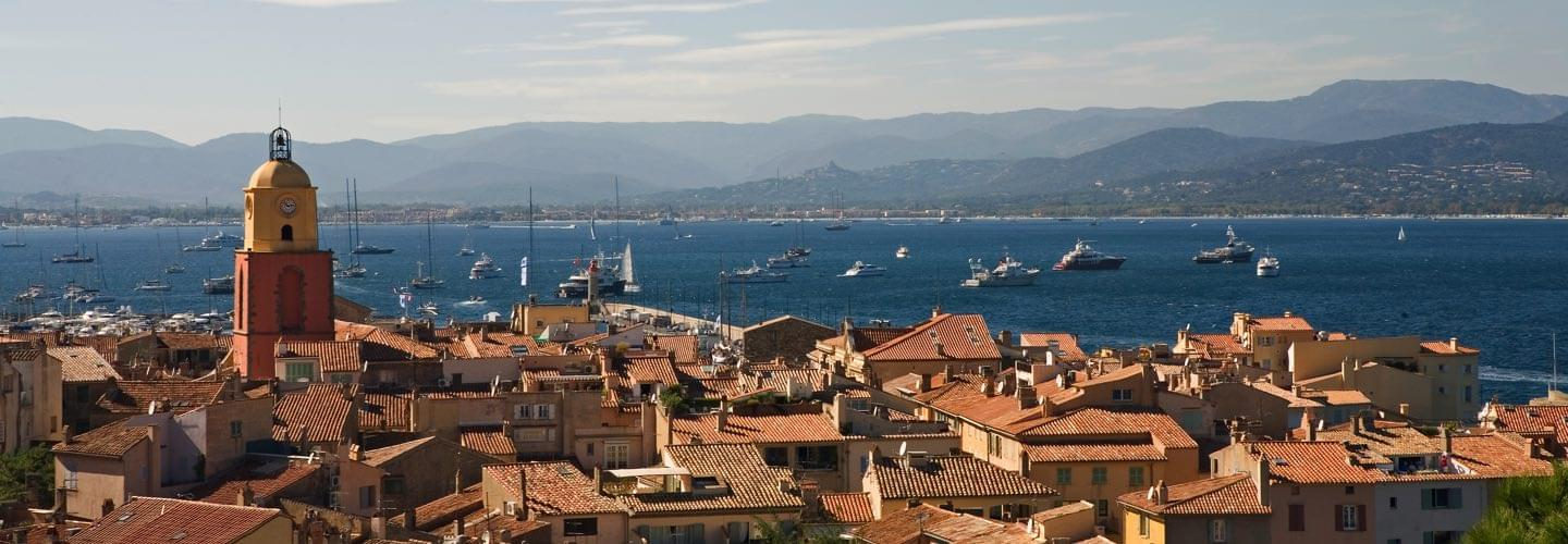 View of red tiles rooftops and Clocher de Saint Tropez and yachts on the Mediterranean sea