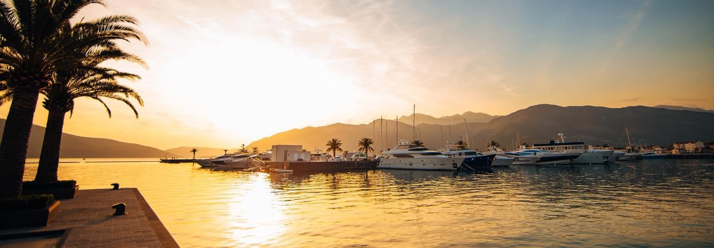 Coucher de soleil à Porto Montenegro à Tivat avec des palmiers et des yachts aux Bouches de Kotor