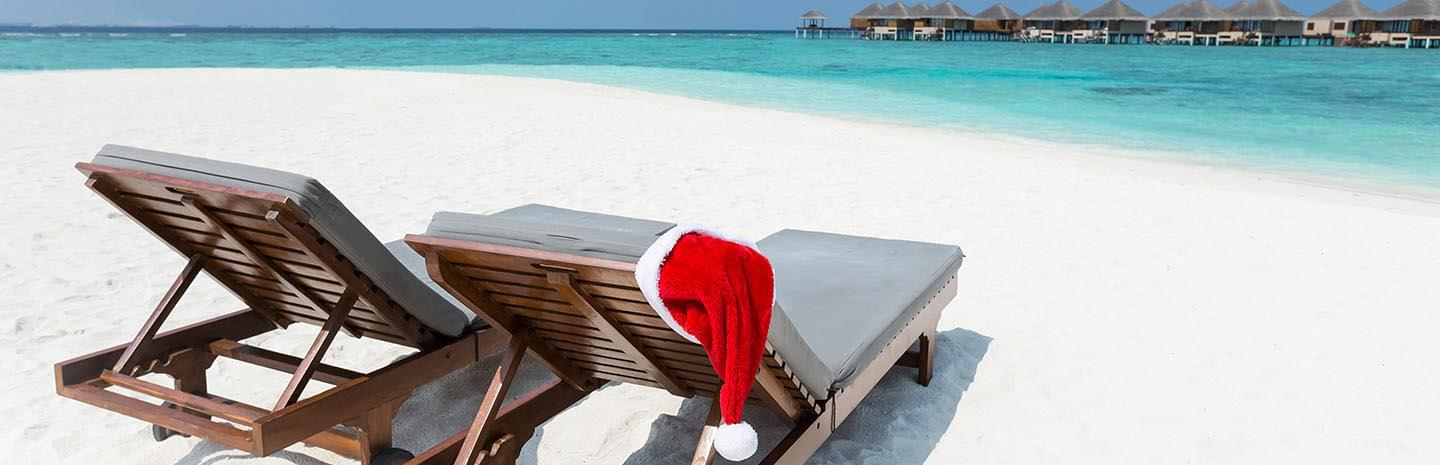 Wooden deckchairs on the beach sand in the bahamas with christmas beanie cap and background sea