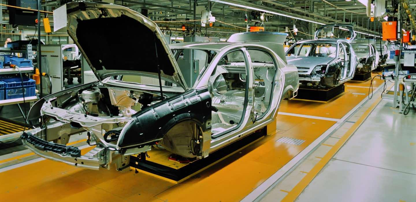 Assembly line of a car factory with yellow ground and a blurred man on the left