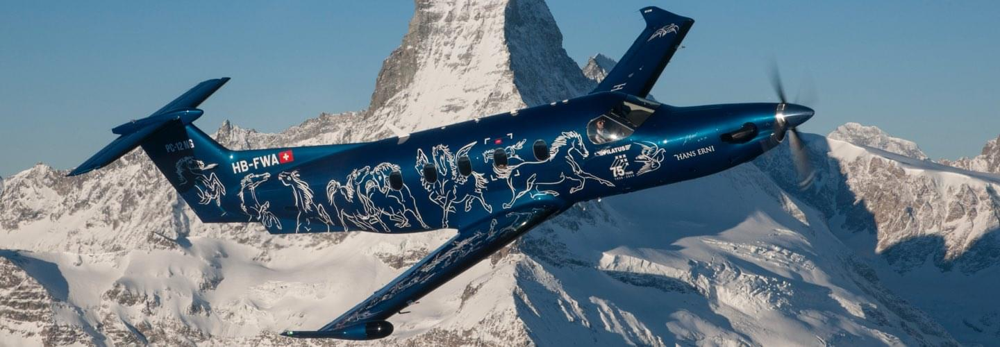 Blue Pilatus PC-12 turboprop with white drowing flying over Swiss snowy mountains