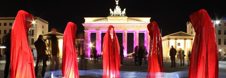 5 silhouettes rouges et photographes au Festival des lumières de Berlin à la porte de Brandenbourg