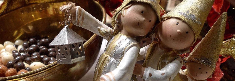 Trois poupées en argile souriantes et chocolats belges au marché de noël de Bruxelles