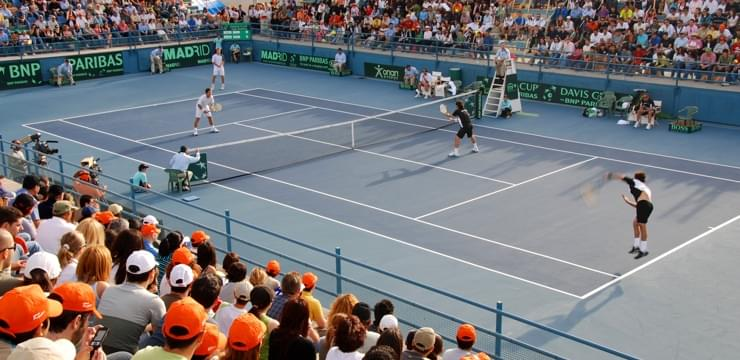 Doubles match at the Davis Cup with the blue tennis court and spectators wearing orange cups