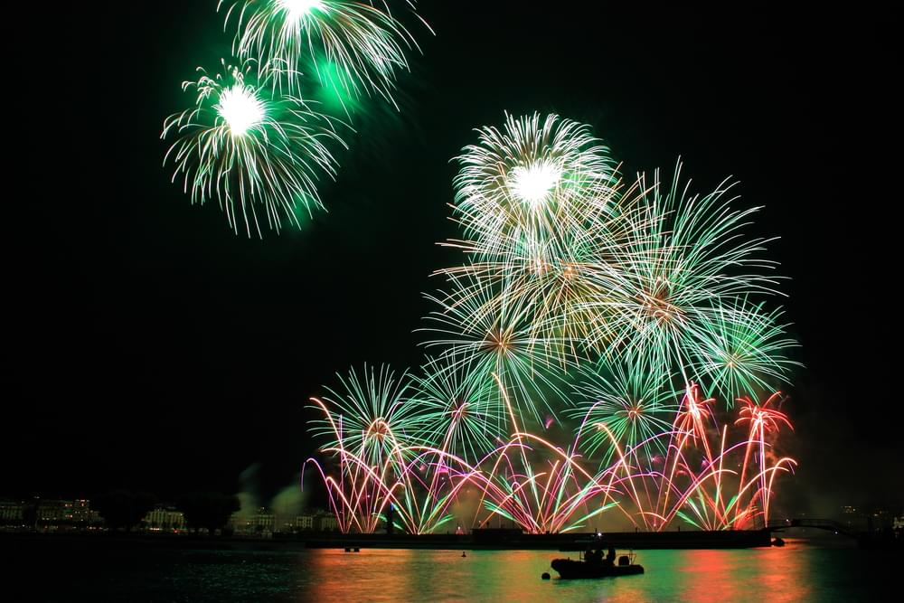 Fireworks at the Geneva Festival with the silhouette of a boat on the lake Léman