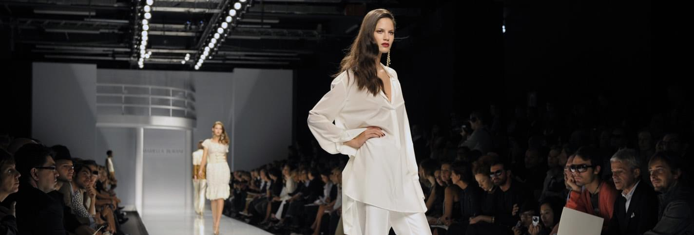 A brunette top model dressed with a white shirt and pants at the Milan Fashion Week