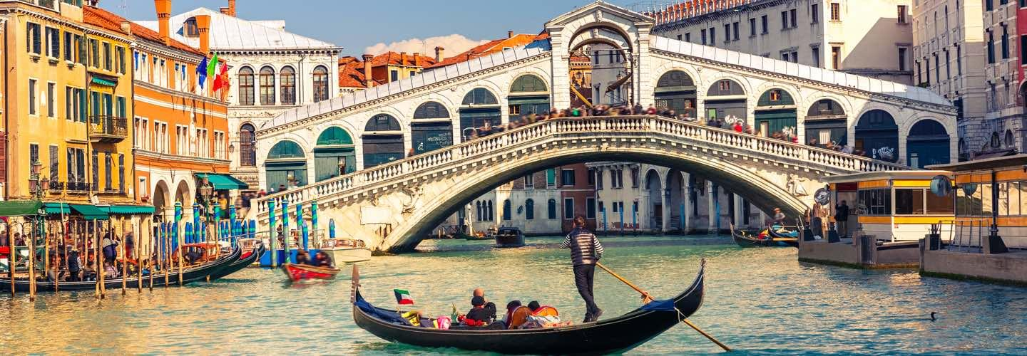 Gondola with tourists in front of the Rialto bridge illustrating the Venice Biennale in Italy