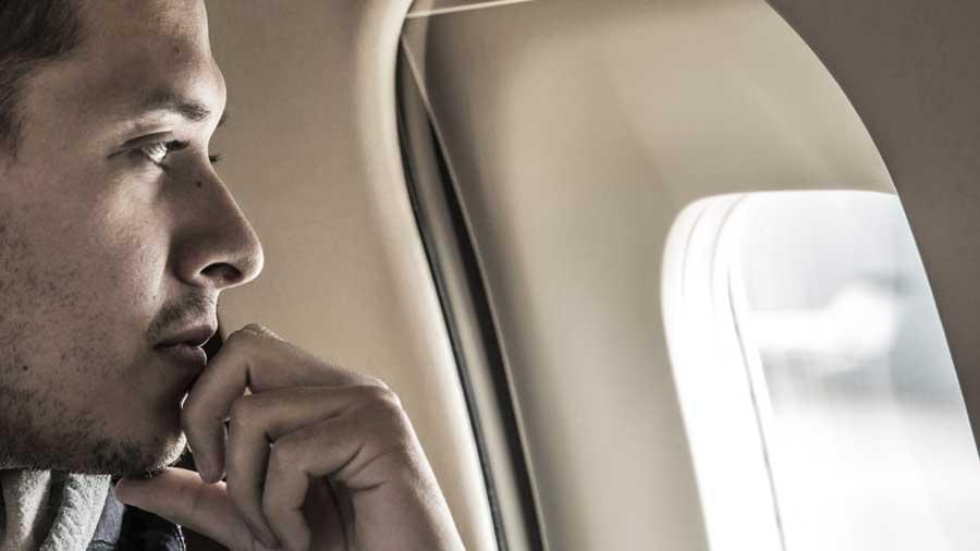 white men looking through a plane porthole