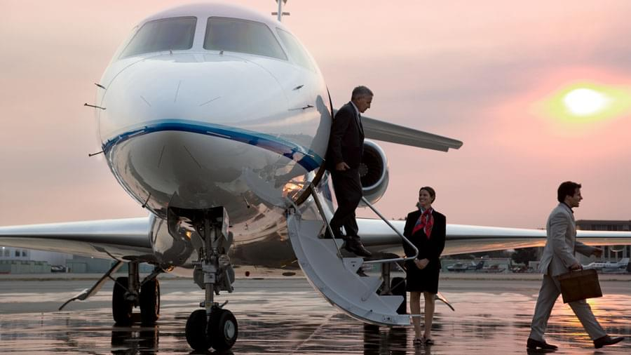 Two business man happily exiting a private jet in the sunset