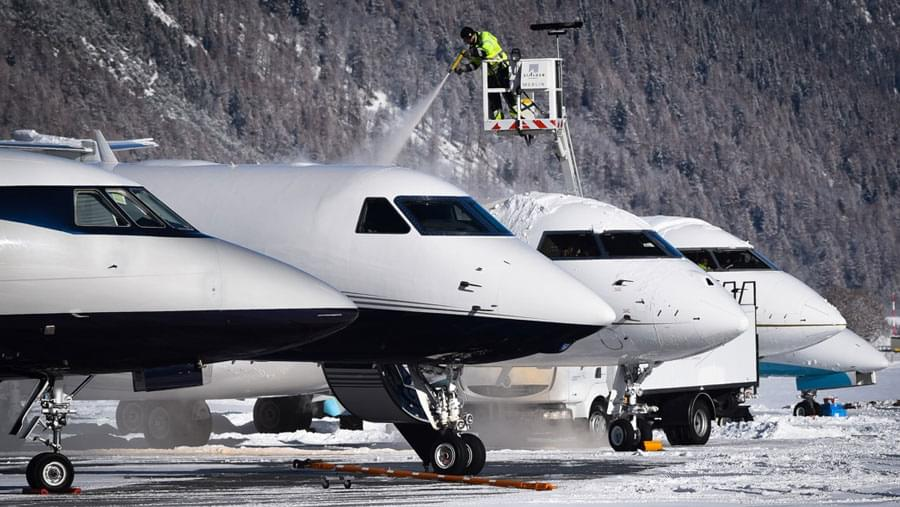 A man removing the ice on the top of an aircraft. This operation is called deicing de-icing