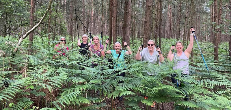 Ladies of different ages smiling in fern bush holding their walking poles
