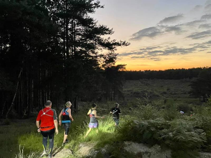 men and woman jogging through the woods with head torches and the sun setting behind them