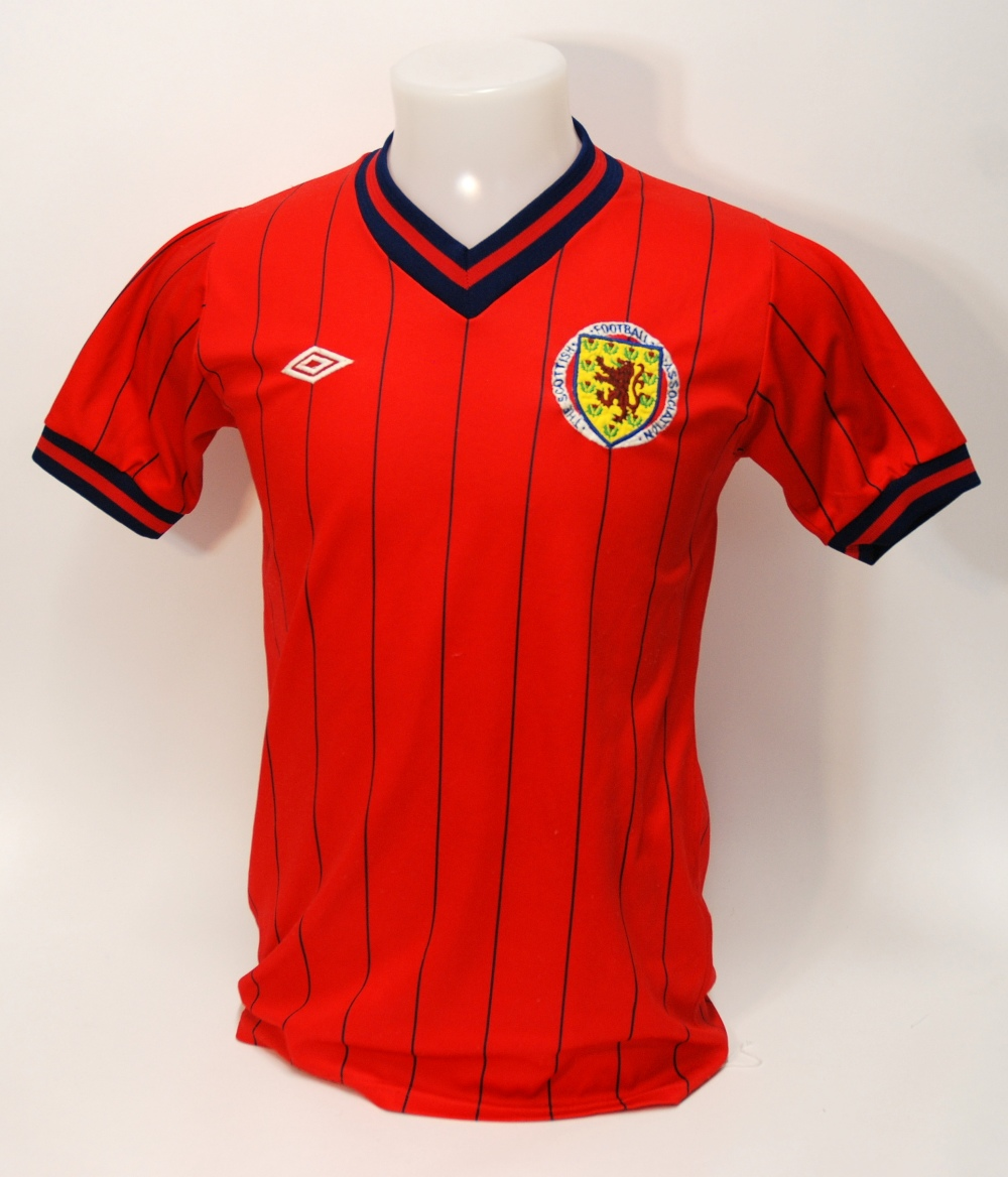 Lot 250 - A red Scotland International short-sleeved shirt No.7, with v-neck collar and embroidered badge,