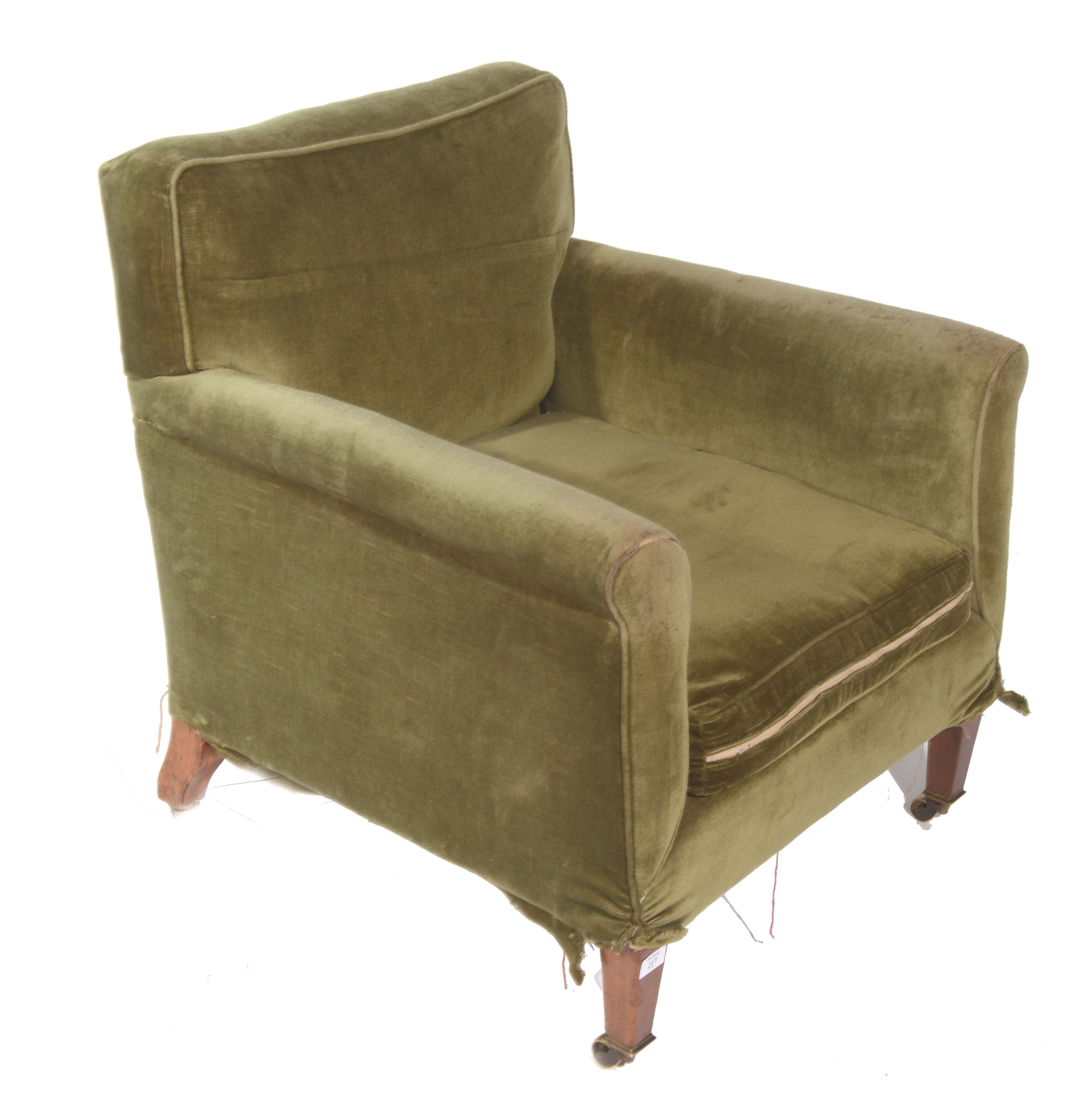 A LOW ARMCHAIR upholstered in green material on four square tapering legs and brass castors