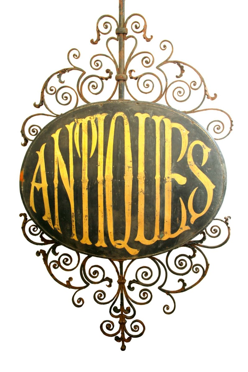 Lot 1951 - A LARGE WROUGHT IRON SHOP SIGN now painted ANTIQUES, set on a black painted copper ground, the