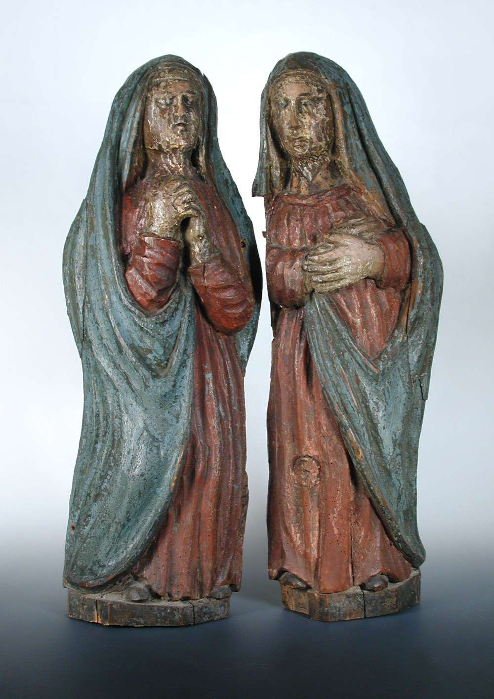A pair of 16th century French polychromed pine figures of female saints wearing blue shawls over