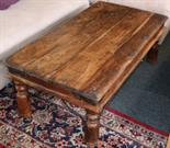 Lot 472 - A 20th Century teak and yew bound low table, raised on turned legs.
