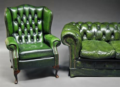 A green leather Chesterfield sofa, 20th century, button back, raised ...