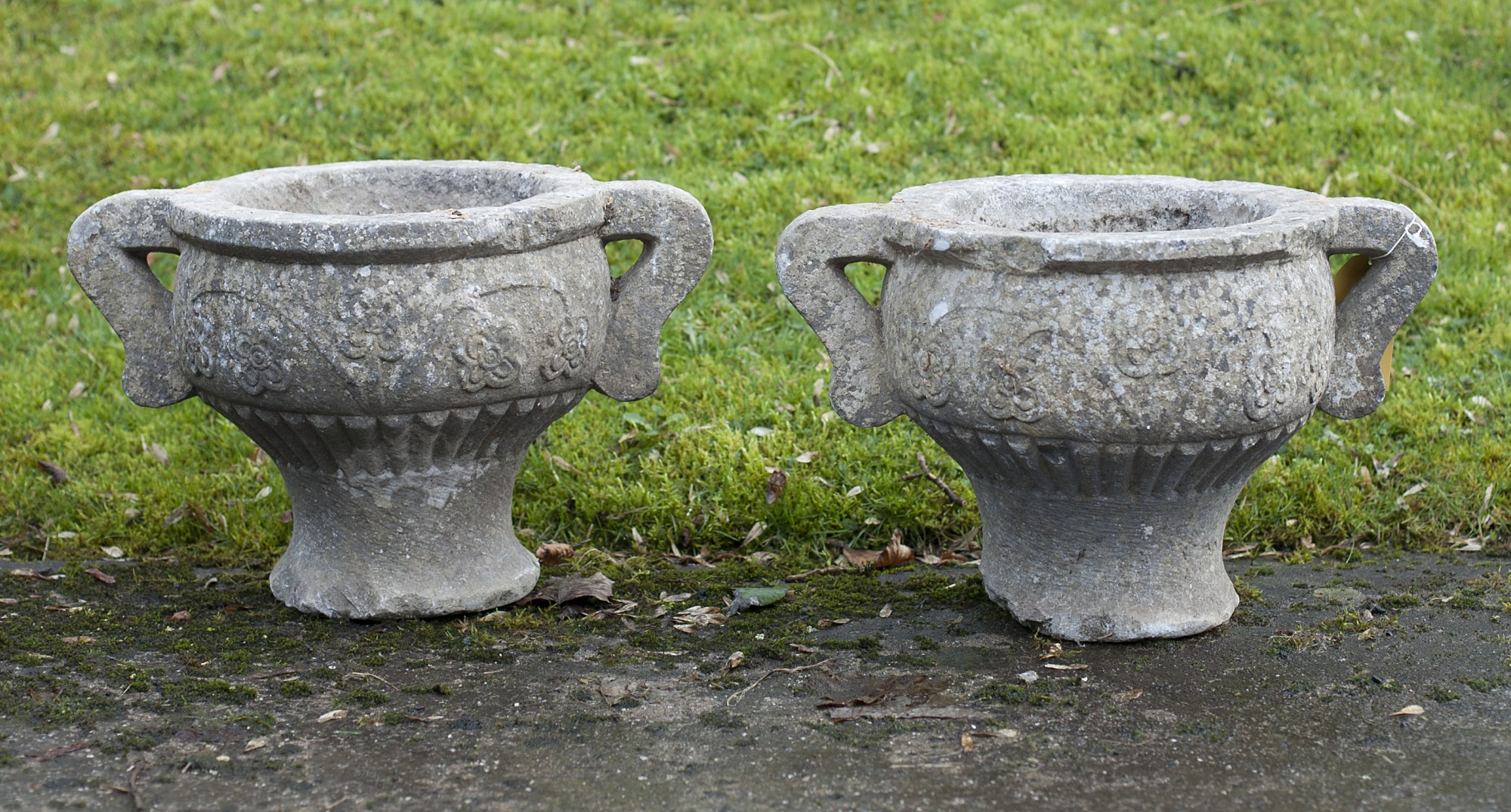 Lot 54 - A very early pair of small carved two handled circular limestone Garden Urns. (2)