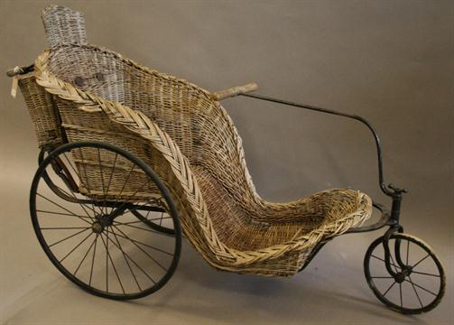 a victorian wicker work bath chair with iron framework and three spoked wheels illustrated