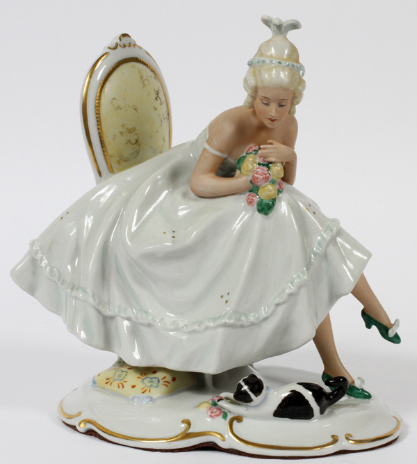 "SCHAUBACH KUNST, GERMAN PORCELAIN FIGURE, C. 1930, H 7 3/4"", W 7"": A young woman seated on a chair"