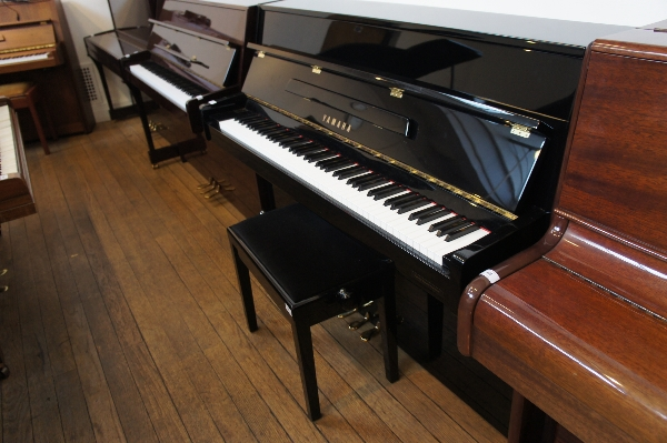 Lot 15 - Yamaha (c2004) A Model C110 upright piano in a bright ebonised case together with a stool.
