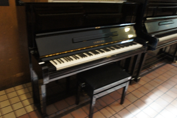 Lot 24 - Yamaha (c1987)  A Model U1A upright piano in a bright ebonised case, together with a matching