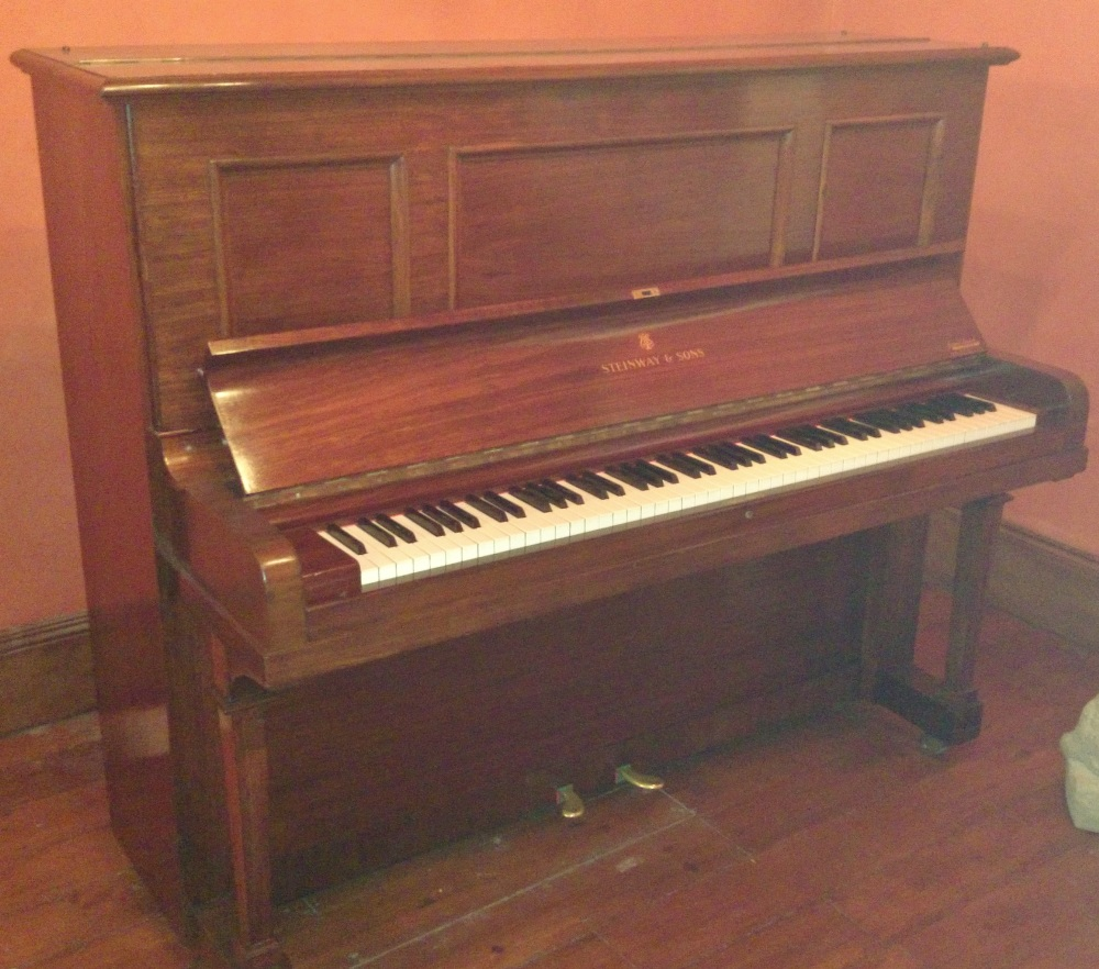 Lot 25 - Steinway (c1920)  A Model K upright piano in a rosewood case. This piano was reconditioned in 1994.
