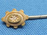 A yellow metal pin stick stamped 15ct having a diamond chip decoration