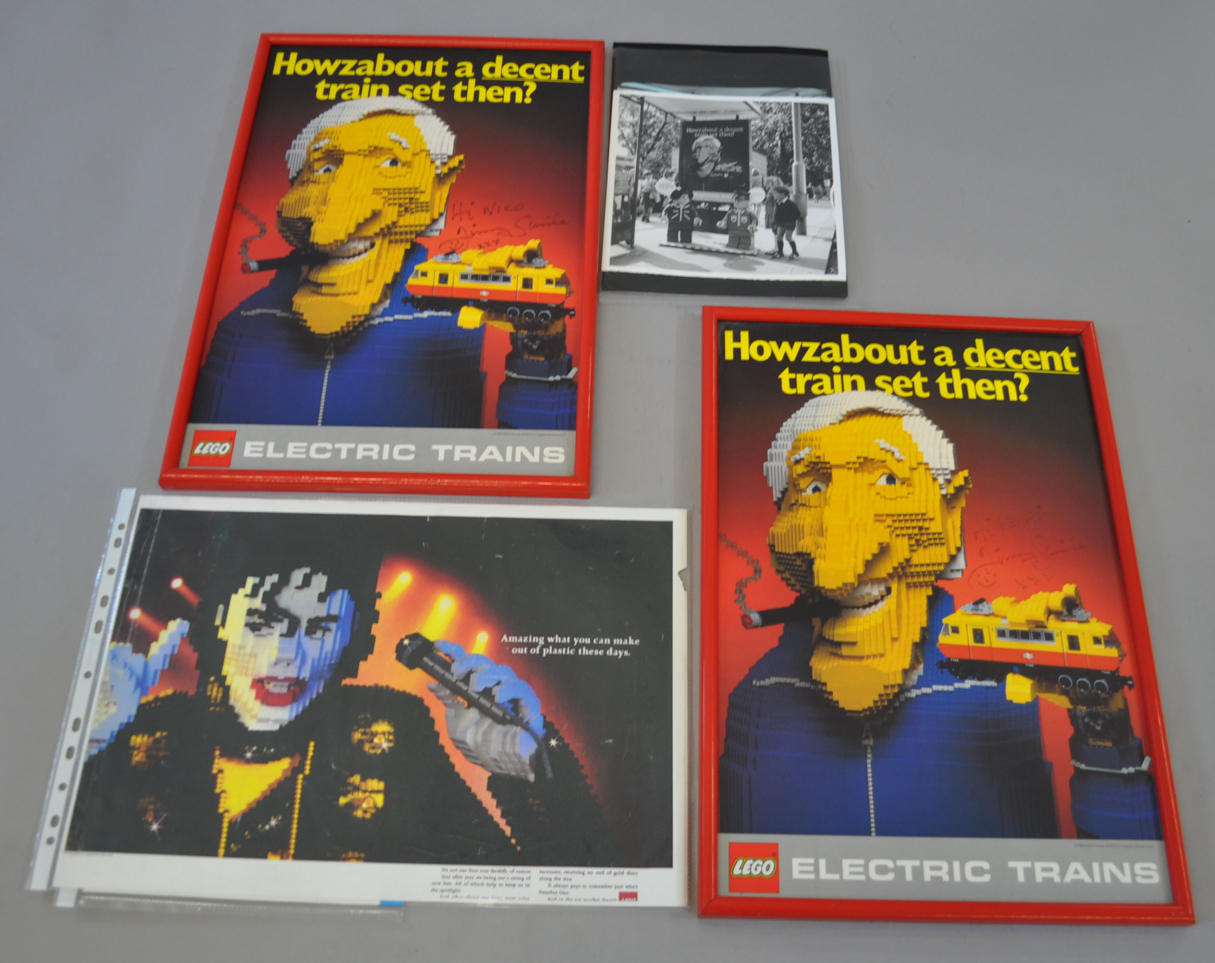 Two framed Lego Electric Trains promotional posters, featuring a Lego model of Jimmy Saville, and