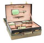 An Art Deco travelling toilet set, green guilloché enamelled silver brushes and bottles in a green
