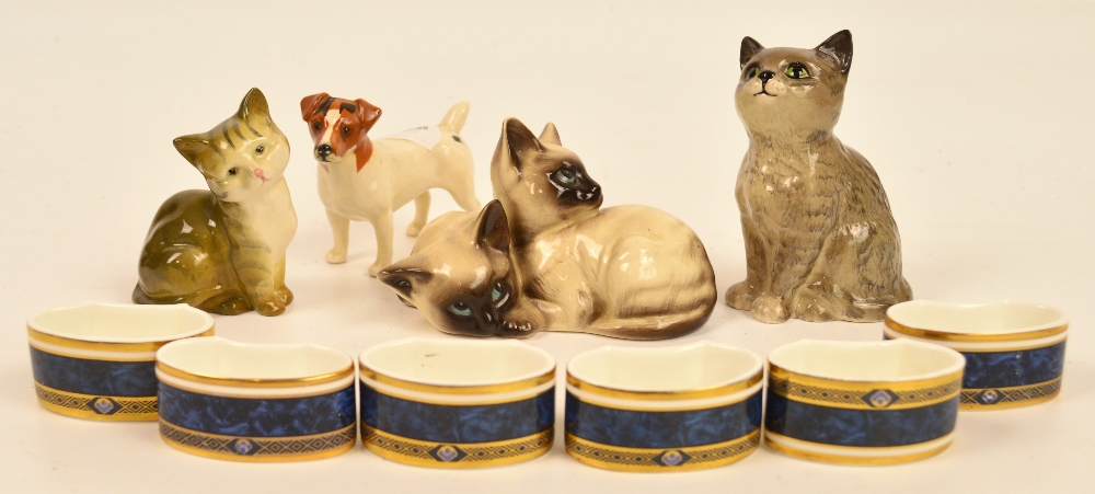 Four Beswick animals comprising two seated cats, a group of two Siamese kittens and terrier, also