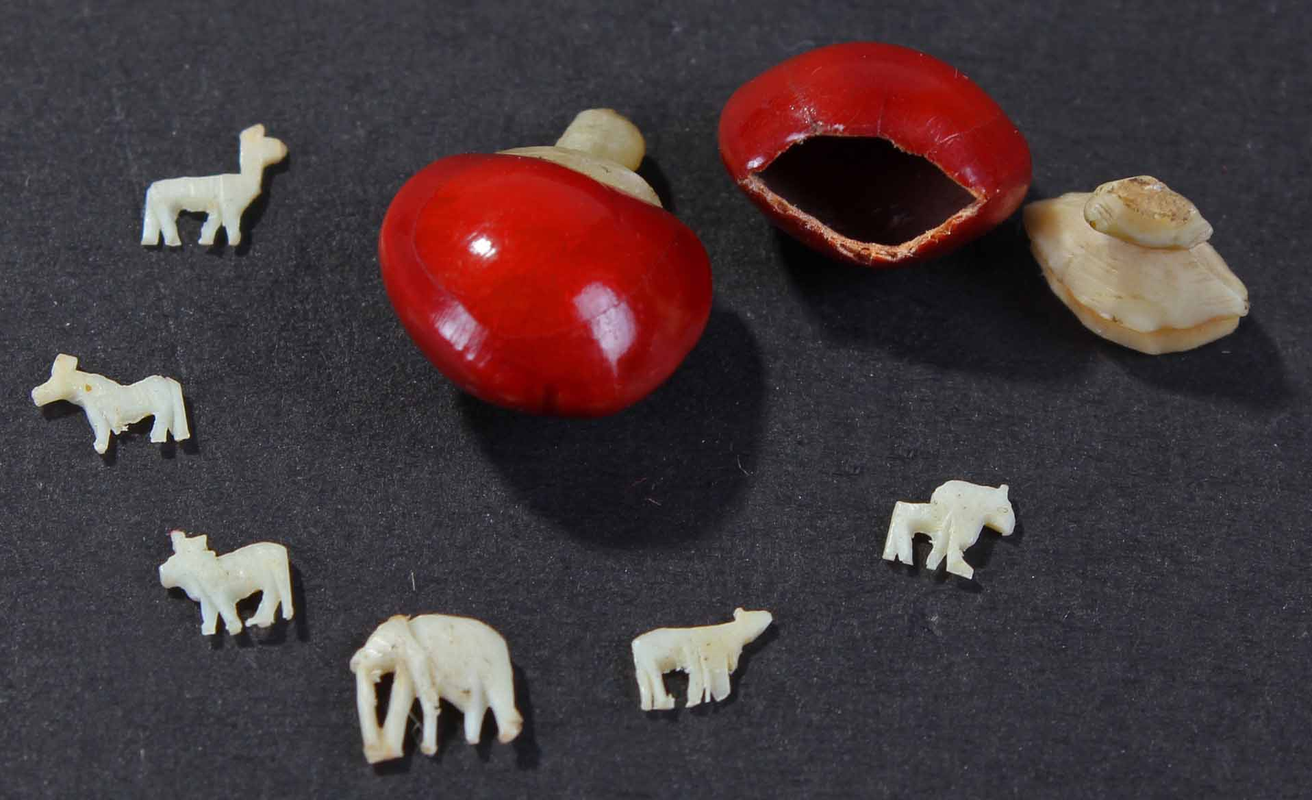 two bean shells with contents of miniature carved ivory
