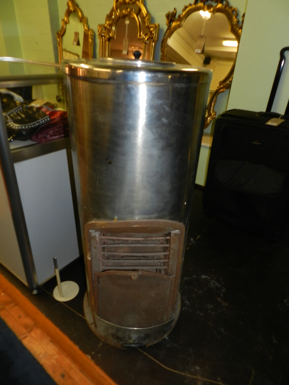 A 'Pither' stainless steel woodburning stove of cylindrical form.