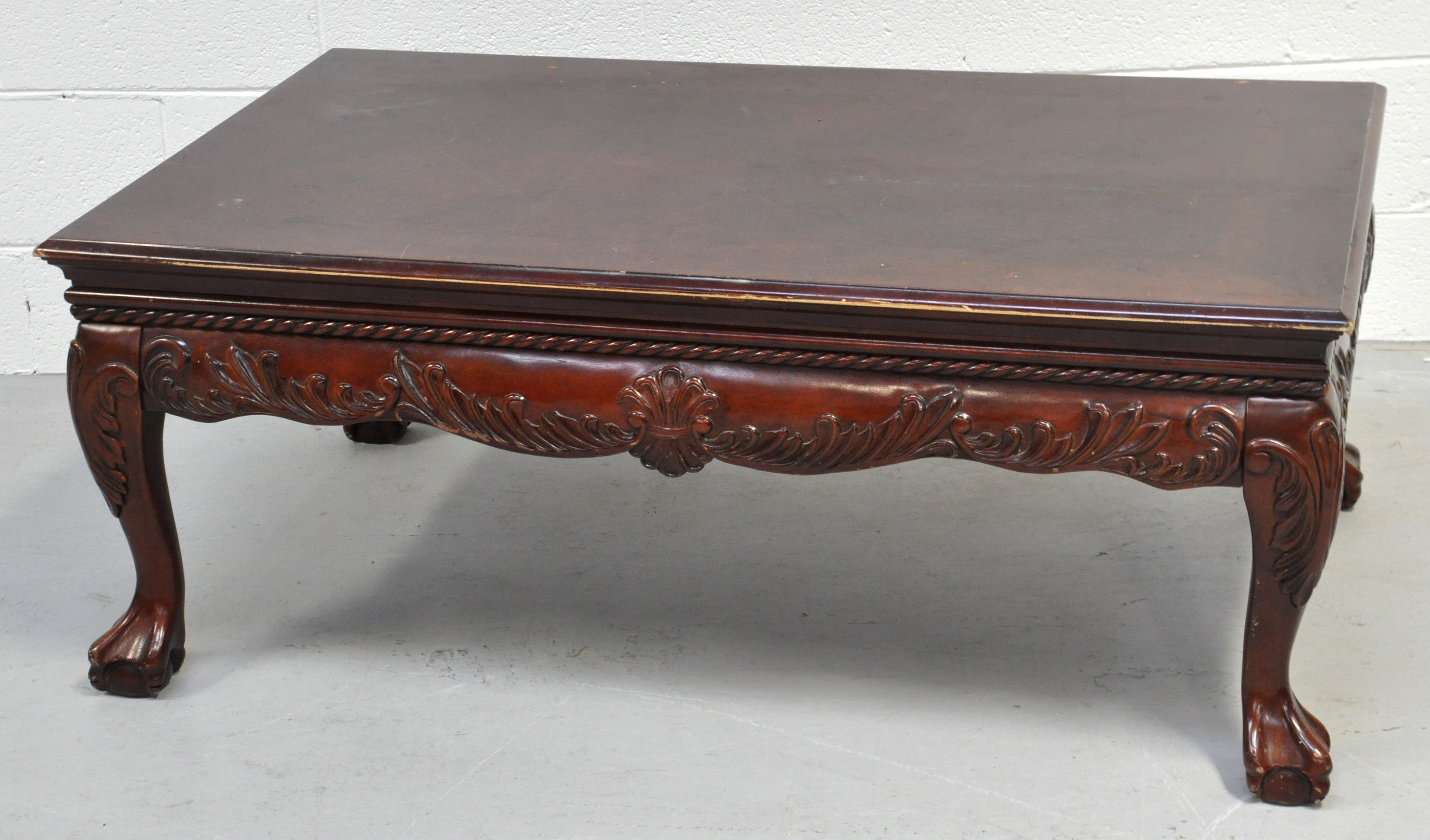 A modern rectangular coffee table with carved frieze cabriole