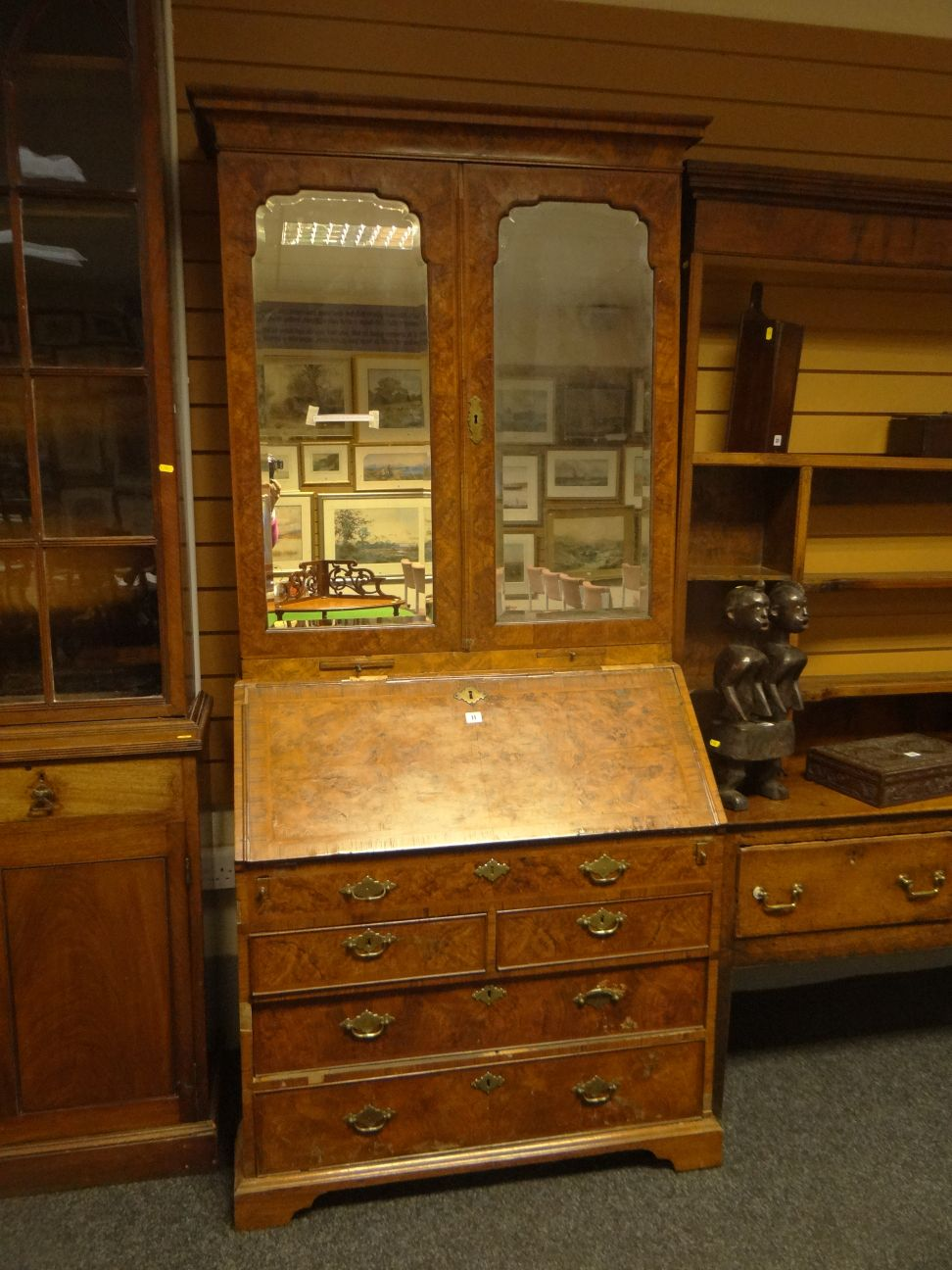 Lot 11 - An early eighteenth century figured walnut bureau bookcase, the upper section having a pair of