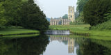 Long view of Fountains Abbey, C12th Cistercian abbey, from Half Moon Pond, showing the Chapel of the Nine Altars and the Tower, their reflection in the water and the weir