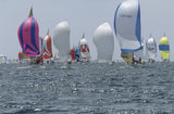 About fifty yachts in the sea at The Isle of Wight, competing in the Round the Island Yacht Race, with their sails billowing towards us