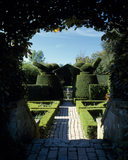 A view of the 'Fushsia Garden' looking through a box hedge archway to the topiary features in the garden