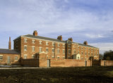 Oblique view of the front facade of the workhouse showing the wall of the exercise yard
