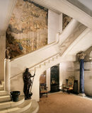 The Tapestry Hall showing the stairs and the Italian C16th carved wood figure of St John the Baptist