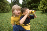 A boy looks through binoculars while a his friend looks over his shoulder at the view. MR
