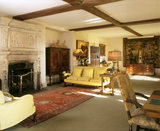 The Living Room from the west end, showing the C17th fireplace and the sofas separated by a Samarkand rug