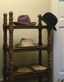 Detail of hats & gloves on a wooden stand in the Map Room