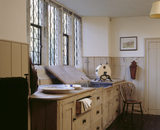 Room view of the Butler's Pantry at Ightham Mote showing the windows, sink, part of radiator and the wooden kitchen cupboards