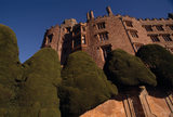 An oblique view of the walls of Powis Castle with a vivid blue sky and green cipped yews